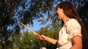 Веселая девушка смеется над и запускается большими пузырями мыла в парке и улыбках города движение медленное акции видеоматериалы