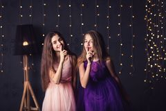 Веселая подруга 2 девушки в пинке и фиолетовых платья показывают shh, в студии на темной предпосылке скопируйте космос Стоковые Изображения