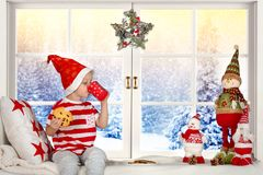 Веселое рождество и счастливые праздники! Небольшой ребенок сидя на окне есть печенья и питьевое молоко стоковое фото rf