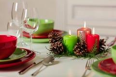 Веселое рождество и С Новым Годом!! Тable устанавливая праздничное оформление - зеленые и красные блюда, свечи и конусы ели Связ стоковые изображения rf