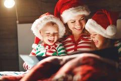Веселое рождество! мать семьи читает к детям книгу перед кроватью в кровати стоковые фотографии rf