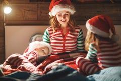 Веселое рождество! мать семьи читает к детям книгу перед кроватью в кровати стоковые фото