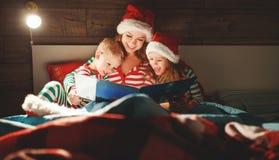 Веселое рождество! мать семьи читает к детям книгу перед кроватью в кровати стоковые изображения rf