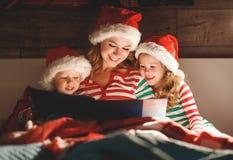 Веселое рождество! мать семьи читает к детям книгу перед кроватью в кровати стоковая фотография