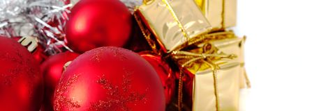 Веселое рождество, Новый Год, подарки в коробках золота, красные шарики рождества сложено в левом угле Белая предпосылка стоковое изображение