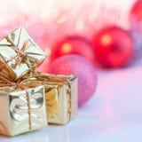 Веселое рождество, Новый Год, подарки в коробках золота, красные шарики рождества сложено в левом угле Предпосылка розова стоковые изображения rf