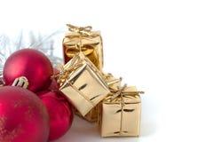 Веселое рождество, Новый Год, подарки в коробках золота, красные шарики рождества сложено в левом угле Белая предпосылка стоковые изображения rf