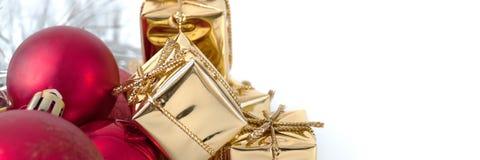 Веселое рождество, Новый Год, подарки в коробках золота, красные шарики рождества сложено в левом угле Белая предпосылка стоковая фотография rf