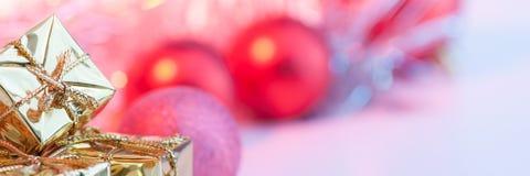 Веселое рождество, Новый Год, подарки в коробках золота, красные шарики рождества сложено в левом угле Предпосылка розова стоковое изображение rf