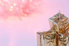 Веселое рождество, Новый Год, подарки в коробках золота, красные шарики рождества сложено в левом угле Предпосылка розова стоковая фотография rf