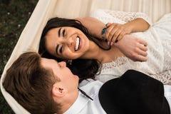 Веселые счастливые молодые пары обнимая в гамаке closeup Стоковое Изображение
