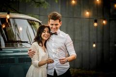 Веселые счастливые молодые пары обнимая около ретро минифургона Конец-вверх стоковые фото