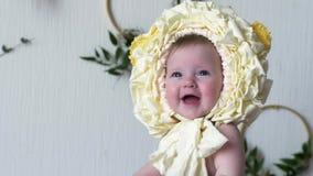 Веселый младенец нося желтый головной убор представляет на камере на крупном плане photoshoot видеоматериал