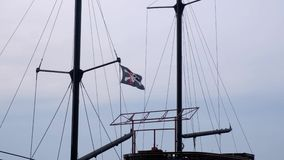 Веселый Роджер флага пирата вися на рангоуте корабля