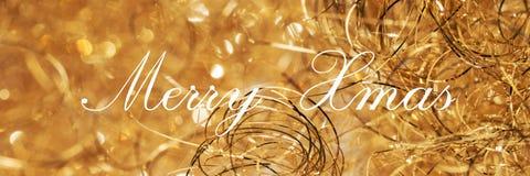 Веселый Xmas, помечая буквами на золотой предпосылке стоковое фото