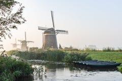 5 весельных лодок в рве на 3 мельницах ветра Molendriegang Leidschendam, Нидерландов во время туманного восхода солнца стоковые фото