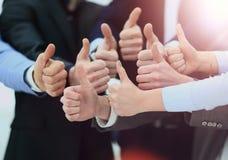 Веселя бизнесмены держа много больших пальцев руки больших пальцев руки вверх Стоковое Изображение