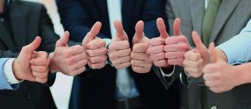 Веселя бизнесмены держа много больших пальцев руки больших пальцев руки вверх Стоковое фото RF