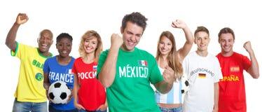 Веселя мексиканский сторонник футбола с вентиляторами от других стран стоковая фотография rf