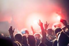 Веселя толпа с руками в воздухе на музыкальном фестивале Стоковые Фото