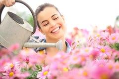 Весеннее время, усмехаясь женщина в маргаритках сада моча Стоковые Изображения RF