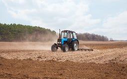Весенний день трактор идет и вытягивает плужок вспахивая поле Стоковое фото RF