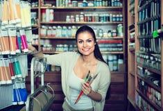 Веселая женщина выбирая различный цвет в трубке Стоковое Фото