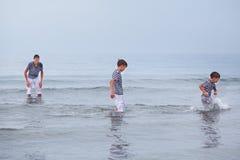 3 веселое, счастливый, брат играют на море Стоковые Фото