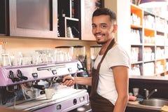 Веселый парень который работая в усмехаться кухни Стоковые Фото