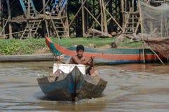 Весельная лодка человека до рыбацкий поселок Камбоджа озера сок Tonle Стоковые Изображения RF