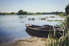 Весельные лодки в тростниках на озере подпирают Стоковые Изображения
