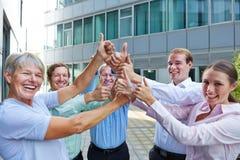 Веселя бизнесмены держа большие пальцы руки вверх Стоковые Фотографии RF