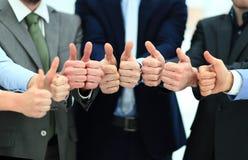 Веселя бизнесмены держа много больших пальцев руки больших пальцев руки вверх Стоковая Фотография