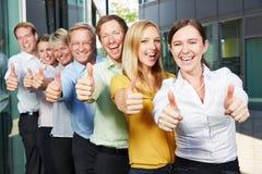Веселя команда дела держа большие пальцы руки вверх Стоковые Изображения