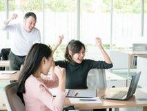 Веселя счастливые бизнесмены, счастливая команда дела с рукой подняли сидеть на столе в офисе во время офиса ежемесячно стоковые изображения