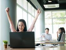 Веселя счастливые бизнесмены, счастливая команда дела с рукой подняли сидеть на столе в офисе во время офиса ежемесячно стоковая фотография rf