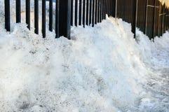 Весна плавя снежок Сугроб грязного снега около загородки металла стоковые изображения rf