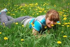 Девушка в одуванчиках Стоковая Фотография