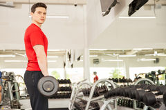 Весы красивого человека поднимаясь в спортзале Стоковые Фото