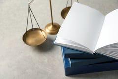 Весы правосудия и книги на таблице Стоковые Фотографии RF