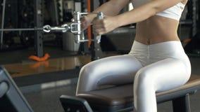 Весы сильной женщины поднимаясь на тренажере в фитнес-клубе стоковое изображение