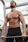 Весы сильного человека пригонки поднимаясь в спортзале Стоковая Фотография