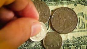 Весьма конец вверх человека кладя монетки на долларовые банкноты