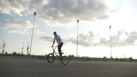 Весьма молодой велосипедист выполняя скачки и маневры вращения работая фокусы ollie для состязания велосипеда - акции видеоматериалы