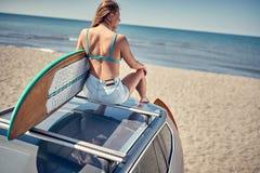 весьма спорт заниматься серфингом девушка серфера сидя на автомобиле и getti стоковая фотография