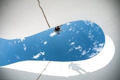 Весьма человек при большой силуэт тени подготавливая для скачки над зазором между бетонными стенами Стоковая Фотография RF