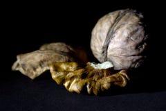 Весь грецкий орех и треснутый грецкий орех на черной предпосылке Стоковая Фотография RF
