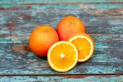 Весь зрелый апельсин 2 приносить с кусками на голубой деревянной винтажной предпосылке Стоковая Фотография RF