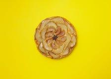 Весь пирог груши яблока Tatin tarte изолированный на желтой предпосылке Стоковая Фотография