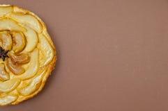 Весь пирог груши яблока Tatin tarte изолированный на коричневой предпосылке Стоковые Фото